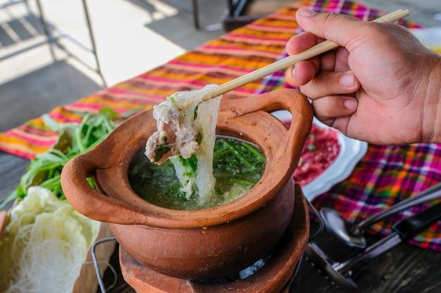 Pentola di terracotta shabu piccante tailandese tradizionale, immersione di carne in zuppa piccante bollita. Foto Premium