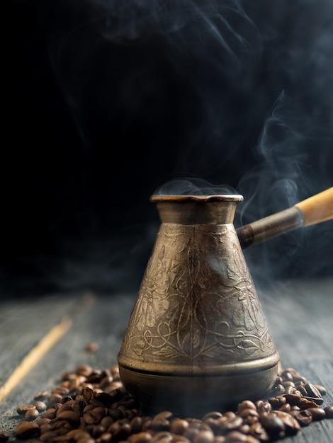 Pentole con caffè appena preparato su uno sfondo scuro con fumo Foto Premium