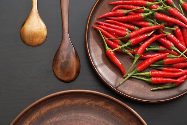 Peperoncini rossi caldi nel piatto marrone delle terraglie Foto Premium