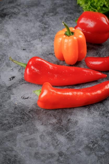 Peperoncini rossi e peperoni dolci sul tavolo di pietra. Foto Gratuite