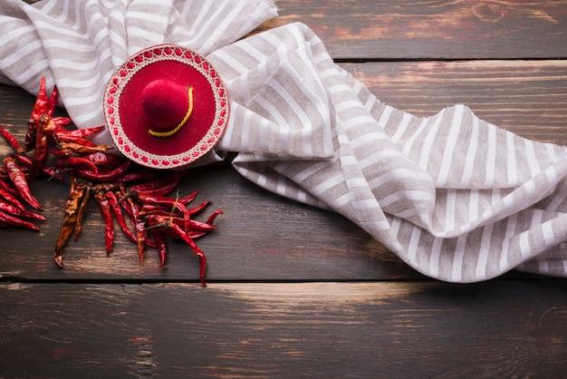 Peperoncino rosso secco sul filo vicino tovagliolo e sombrero decorativo Foto Gratuite