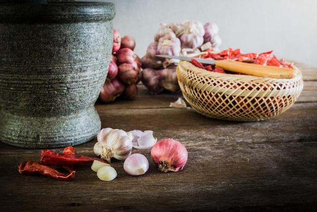 Peperoncino secco e cipolla rossa e aglio e pietra mortaio su un vecchio fondo di legno Foto Premium