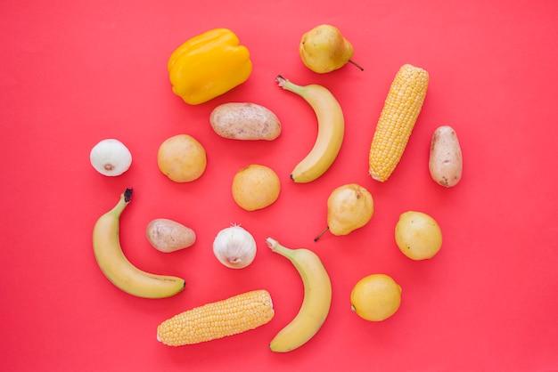 Peperone giallo; cipolla; patata; pere; lime; mais e aglio su sfondo rosso Foto Gratuite