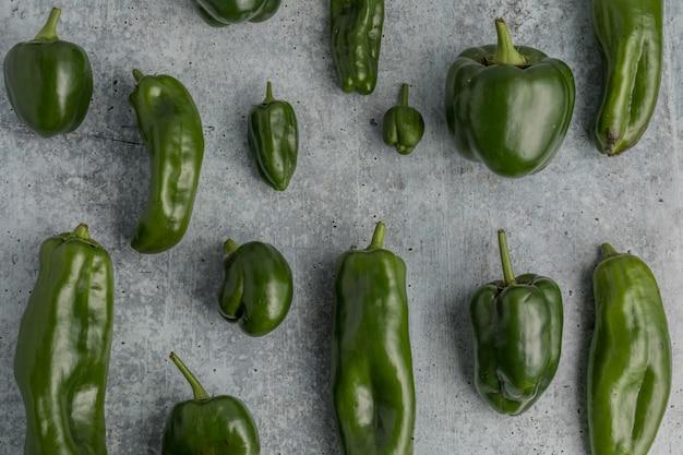 Peperoni dolci verdi su terra grigia Foto Gratuite