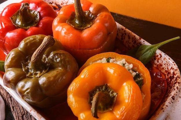 Peperoni fatti in casa, ripieni. con un ripieno di basilico, spinaci, formaggio e spezie. con sugo di pomodori freschi fatti in casa. realizzato in stile rustico. Foto Premium