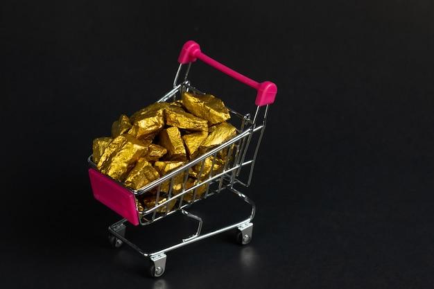 Pepite d'oro o minerale d'oro nel carrello o nel carrello del supermercato Foto Premium