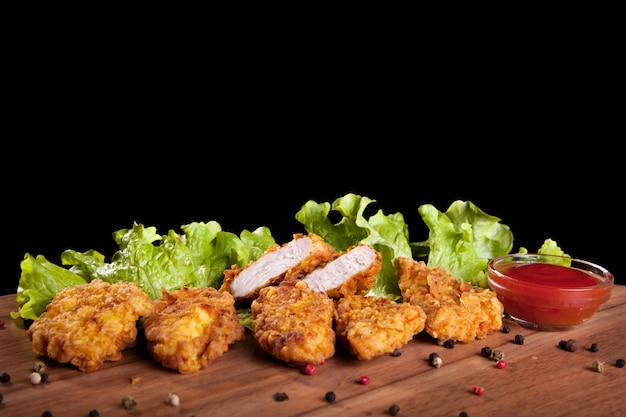 Pepite di pollo, su un tavolo di legno con salsa e lattuga su sfondo nero. Foto Premium