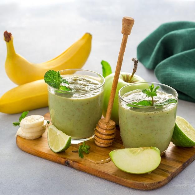 Perdita di peso pulito mangiare cibo sano dieta disintossicazione bevanda frullato verde di mela banana lime Foto Premium