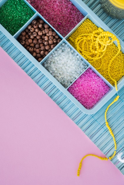 Perle colorate in caso blu su placemat sopra lo sfondo rosa Foto Gratuite