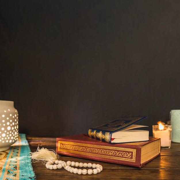 Perle e libri vicino a lanterna e candela Foto Gratuite