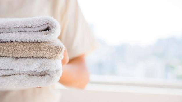 Persona anonima con pila di asciugamani in spugna Foto Gratuite