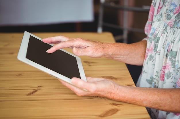 Persona anziana che tocca una compressa digitale Foto Premium