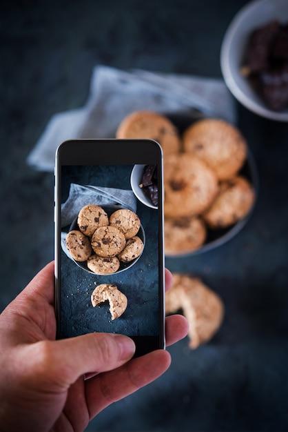 Persona che cattura l'immagine con un telefono ad alcuni biscotti con cioccolato Foto Premium
