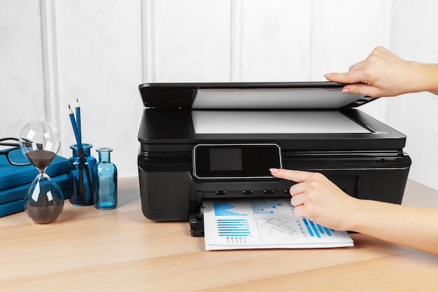 Persona che fa copie sulla fotocopiatrice in ufficio Foto Premium