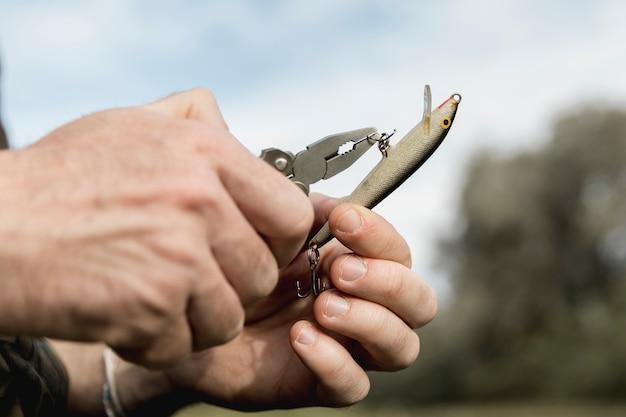 Persona che fissa un amo da pesca Foto Gratuite