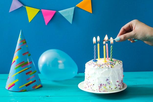 Persona che illumina torta fatta in casa scaricare foto gratis