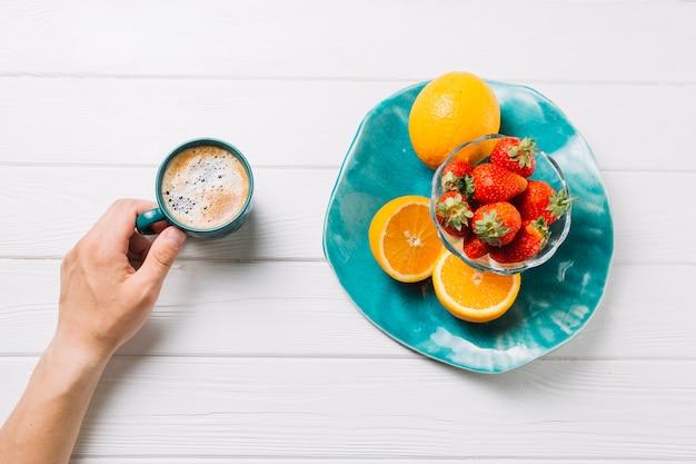 Persona che mangia frutta biologica e gustosa bevanda su sfondo bianco strutturato Foto Gratuite