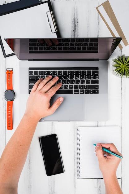Persona che prende appunti utilizzando un computer portatile e un blocco note Foto Gratuite