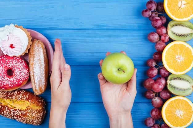 Persona che sceglie cibo sano sopra i dolci Foto Gratuite