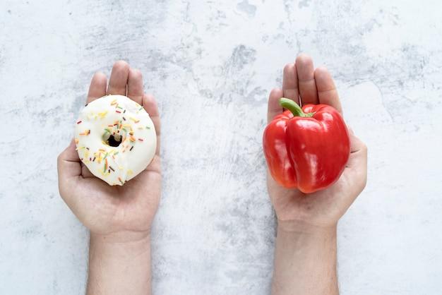Persona che sceglie tra bellpepper e ciambella su sfondo con texture Foto Gratuite