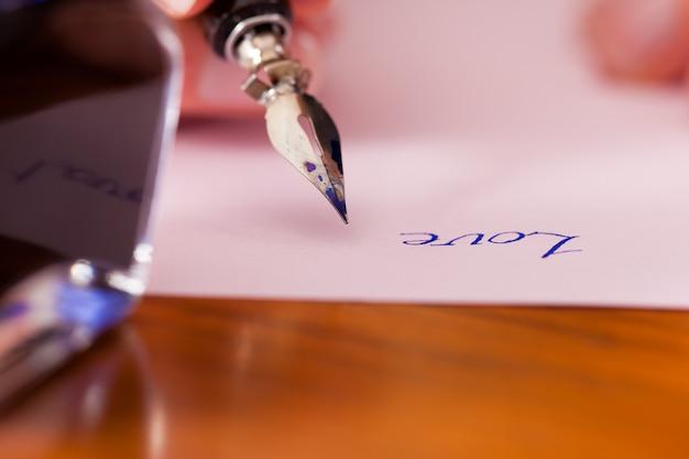 Persona che scrive una lettera d'amore con penna e inchiostro Foto Premium