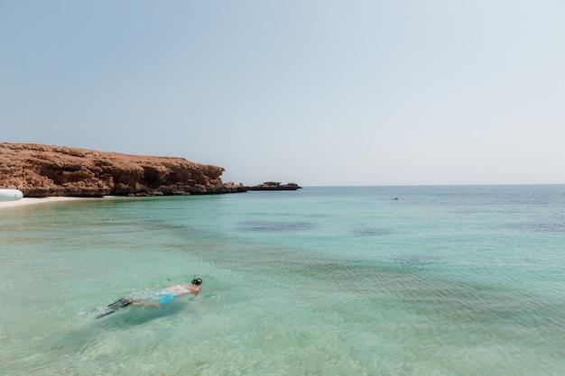 Persona che si tuffa nel mare vicino alle scogliere rocciose sotto il chiaro cielo blu Foto Gratuite