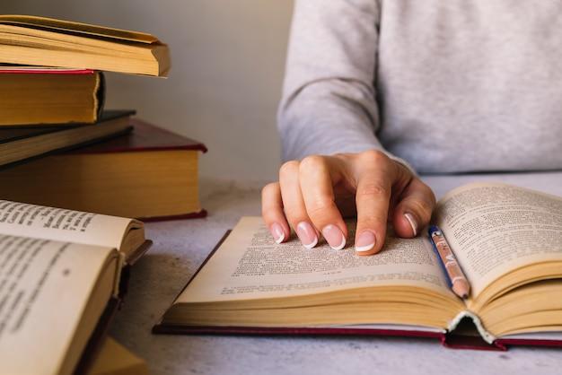 Persona che studia accanto al mucchio del libro Foto Gratuite