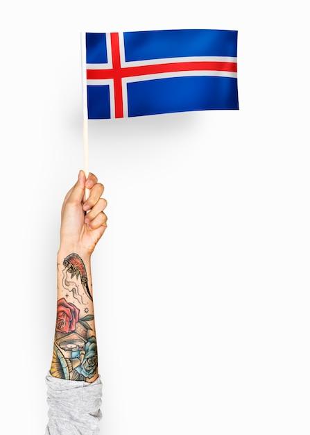 Persona che sventola la bandiera dell'islanda Foto Gratuite