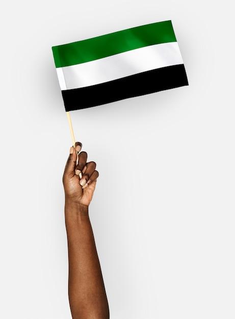 Persona che sventola la bandiera dello stato islamico dell'afghanistan Foto Gratuite