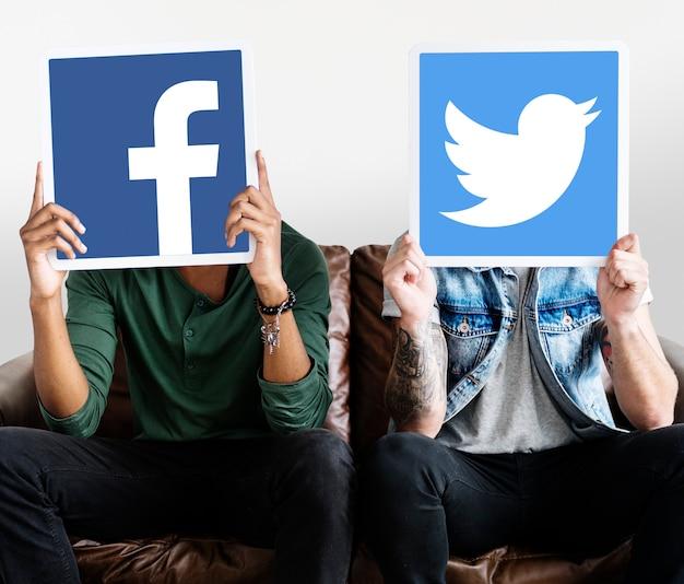 Persona che tiene due icone social media Foto Gratuite