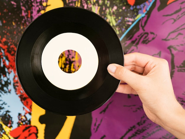 Persona che tiene il retro disco del vinile vicino al hol multicolore di wallperson Foto Gratuite