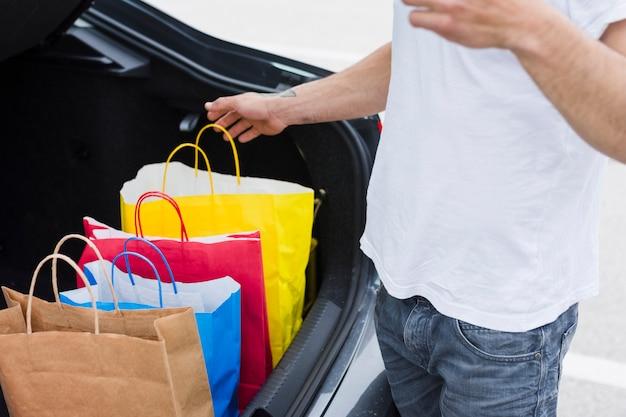 Persona che tiene le borse della spesa all'interno dell'auto Foto Gratuite