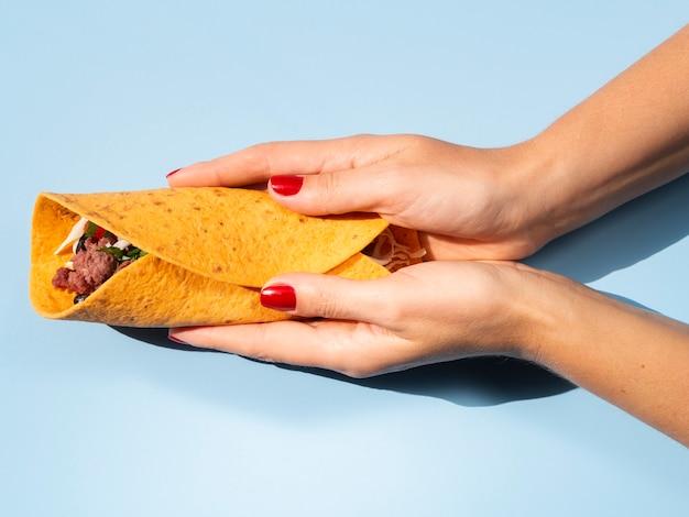 Persona del primo piano con burrito delizioso e fondo blu Foto Gratuite