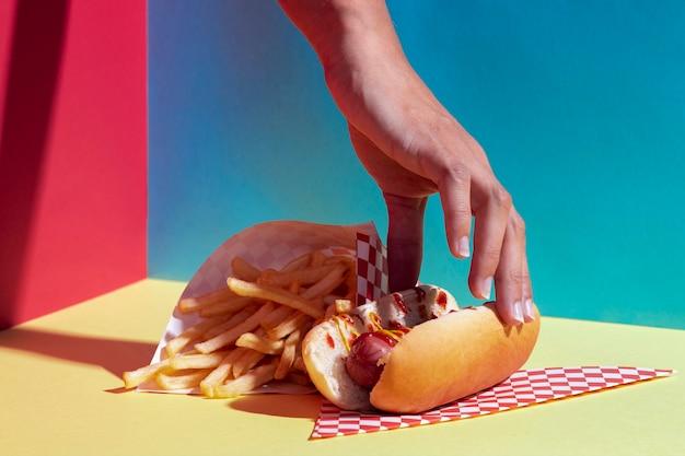 Persona del primo piano con hot dog e patatine fritte Foto Gratuite