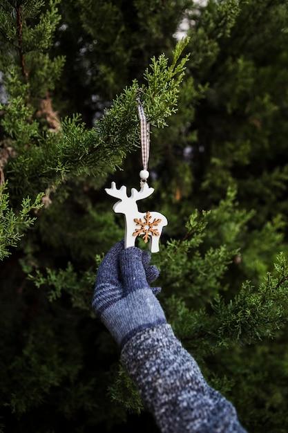 Persona del primo piano con i guanti che tengono decorazione a forma di renna Foto Gratuite