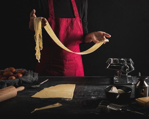 Persona del primo piano con la pasta rossa della tenuta del grembiule Foto Gratuite