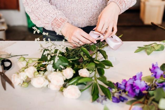 Persona di vista frontale che prepara mazzo di fiori Foto Gratuite