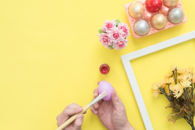 Persona di vista superiore che dipinge l'uovo di pasqua variopinto dipinto in composizione in colori pastello con il pennello Foto Gratuite