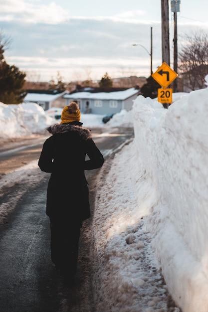 Persona in cappotto nero che sta sulla strada innevata durante il giorno Foto Gratuite