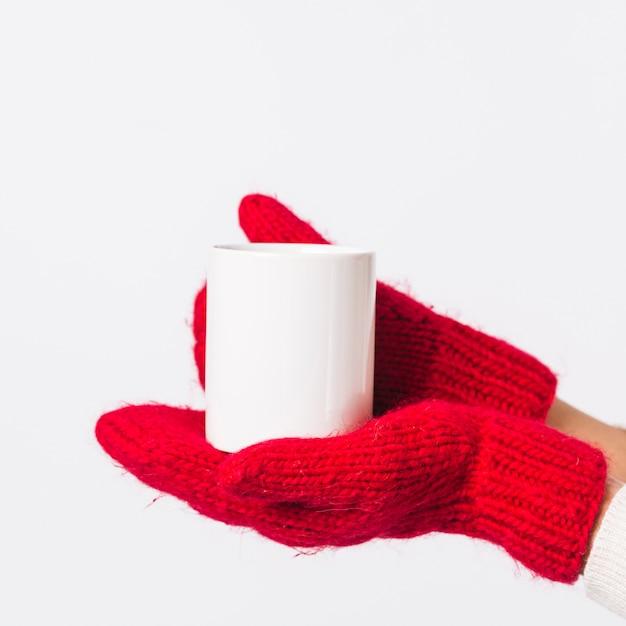 Persona in guanti che tiene tazza Foto Gratuite