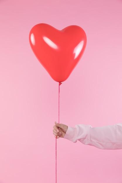 Persona in possesso di palloncino rosso con filo Foto Gratuite