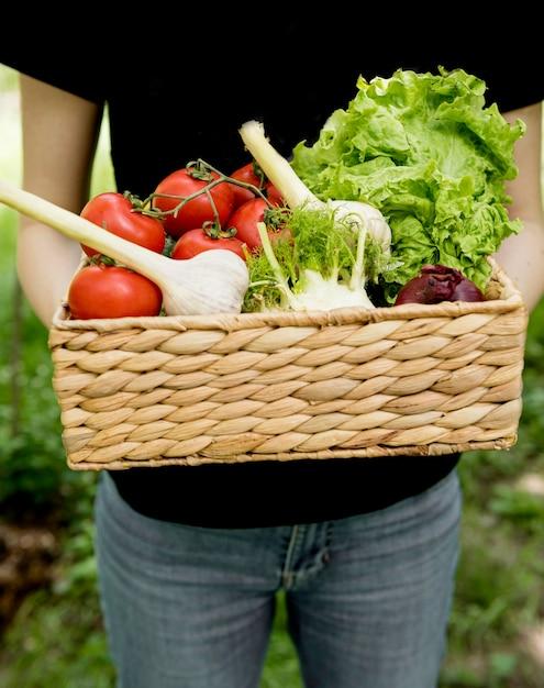 Persona in possesso di secchio con verdure Foto Gratuite