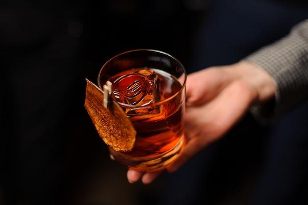 Persona in possesso di un bicchiere di whisky con ghiaccio Foto Premium