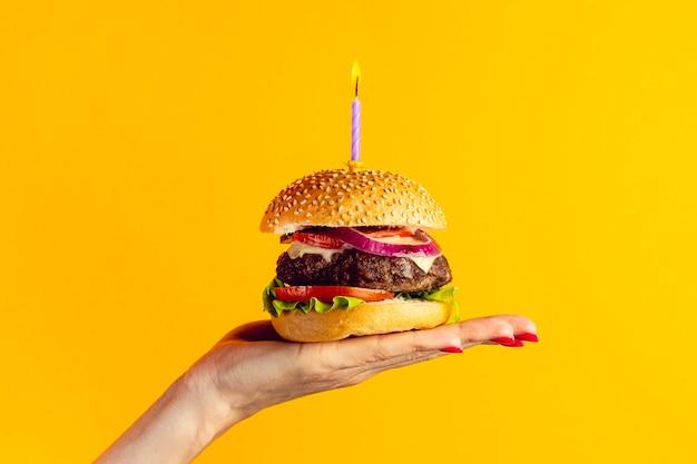 Persona in possesso di un hamburger dell'anniversario Foto Gratuite