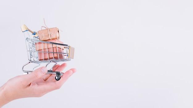 Persona in possesso di un piccolo carrello della spesa con scatole regalo Foto Gratuite