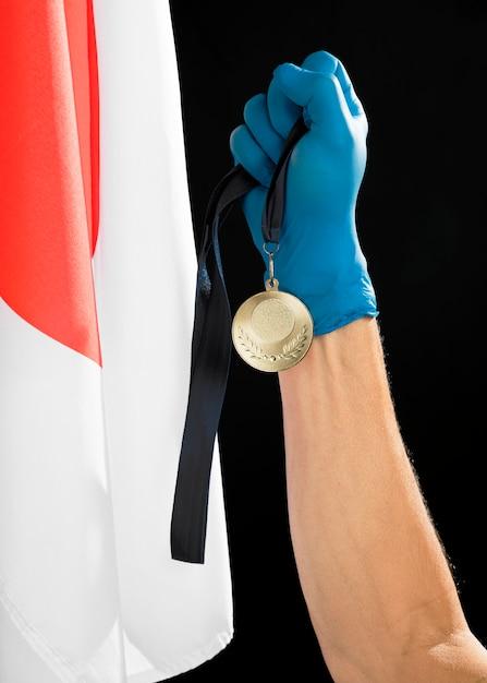 Persona in possesso di una medaglia d'oro Foto Gratuite