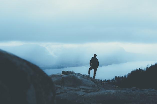 Persona in un cappotto caldo in piedi su una montagna rocciosa e guardando gli alberi Foto Gratuite