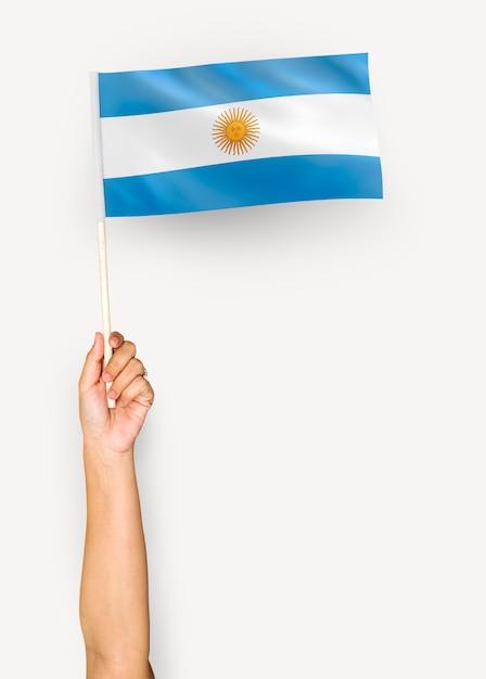 Persona sventolando la bandiera della repubblica argentina Foto Gratuite