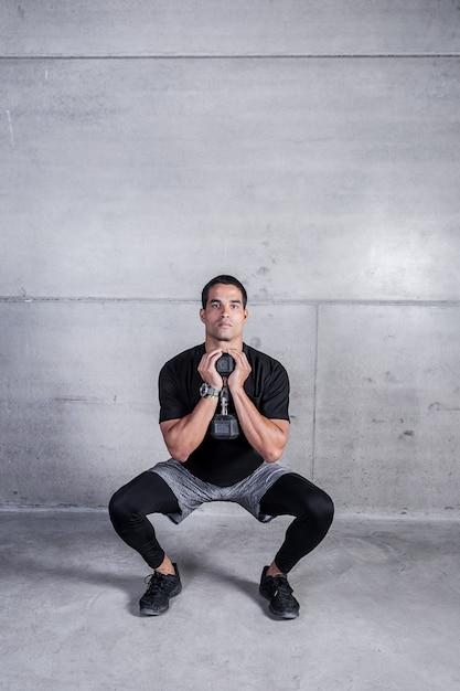 Personal trainer facendo squat con manubri Foto Premium