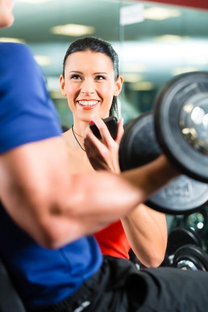 Personal trainer in palestra e allenamento con manubri Foto Premium